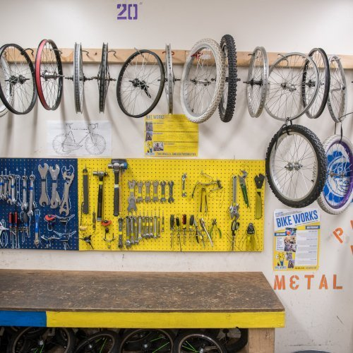 A row of bike wheels suspended from a white wall, with a blue and yellow board below it full of wrenches and other bike repair tools